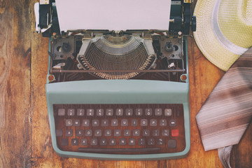 vintage typewriter with blank page on wooden table