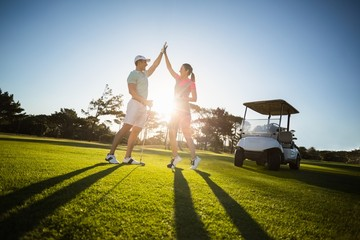 Happy golf player couple giving high five
