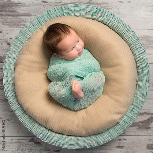 12ed066fa wrapped newborn baby with bare foot lying in round cot