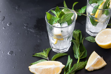 glasses with ice and lemon, mint and ice on a black background