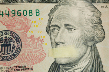 American leader Alexander Hamilton with mouth glued on the banknote of ten dollars USA