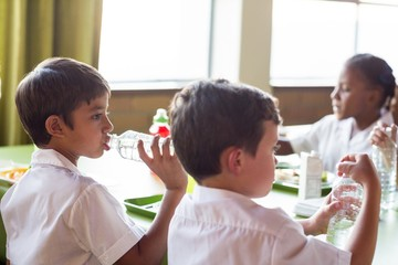 Schoolboy drinking water from bottle