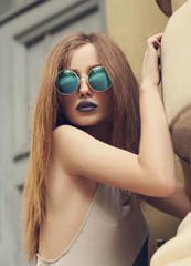 Portrait of fashion lady with blue lips in round sunglasses