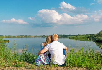 young couple sitting in summer near lake