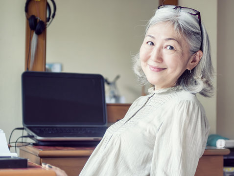 Asian senior woman leaned back in her chair and smiling