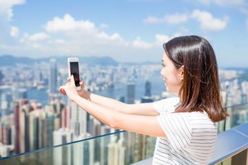 Woman taking photo of Hong Kong city