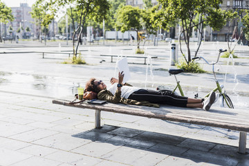 Young woman lying on a bench reading notes