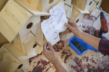 Man assembling birdhouses in workshop holding plan