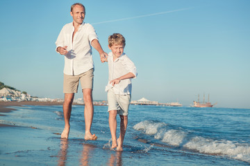 Father with son running together on the sea surf line