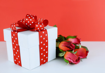 White, square gift box decorated with red and white polka dot ribbon on white table with red background. Silk red roses are laying beside the box. Copy space.