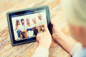 senior woman with family photo on tablet pc screen