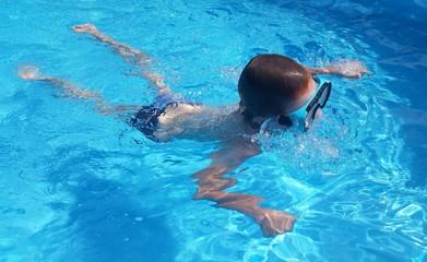 Kind schwimmt im Pool mit Taucherbrille