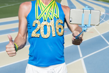 Athlete standing at the running track taking a selfie on his mobile phone with selfie stick of his 2016 gold medal