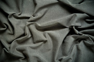 Dark wrinkled fabric texture. Close-up of soft cotton cloth, may be used as background.