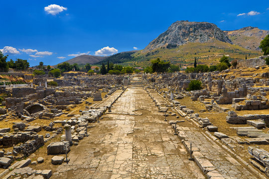 Greece. The Archaeological Site of Ancient Corinth. Lechaion Road (cardo maximus) paved with limestone slabs and remains of monuments. There is Acrocorinth with fortified citadel in the background