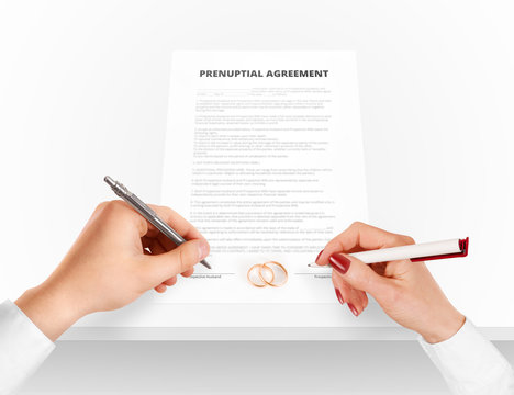 Man and woman sign prenuptial agreement near gold rings. Legal prenup document contract signing by newlywed couple. Marry partners signature on prenupt statement. Wedding ceremony conflict text.