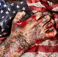 Human hand of hero in blood protect american flag
