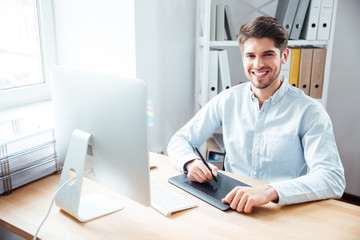 Smiling man designer working and using graphic tablet in office