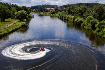 Jet ski turns with much splashes on the river.