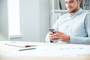 Cropped image of a businessman sitting and using smartphone