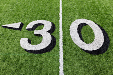 30 yard line on a green football field with white lettering