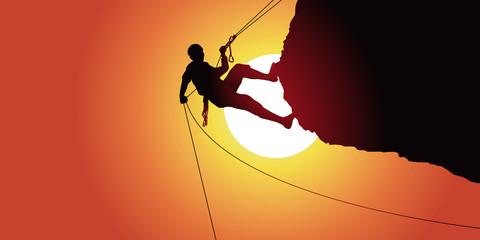 descente en rappel d'un alpiniste après une escalade un rocher en surplomb sous un soleil