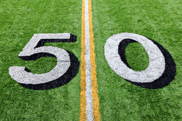 50 yard line on a green football field with white lettering