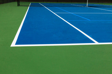 Blue tennis court surface with green texture, white lines and black net