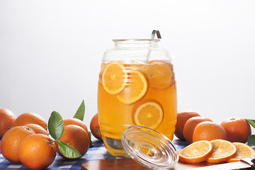 A jug of orange lemonade with fresh oranges.