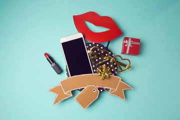 Smartphone with cardboard banner, lipstick and gift box. Creative website hero image. View from above