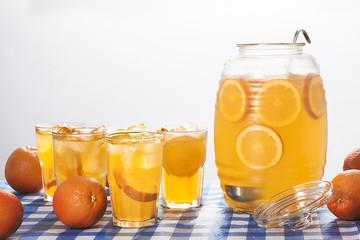 A jug and glasses of orange lemonade with fresh oranges.