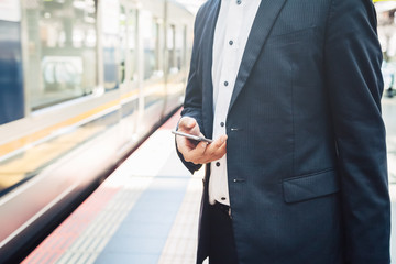 Businessman looks smartphone awaiting the arrival of train at the station