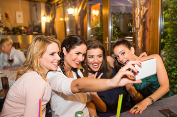 Young beautiful women in bar taking selfie
