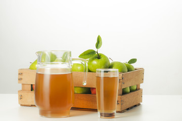 Pitcher and glass of apple juice and fresh apples in a wooden box.
