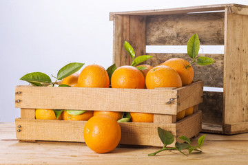 Oranges with leaves in a wooden box.