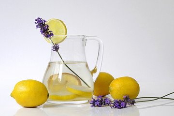 Fresh lemonade in a glass jug with slices, decorated with whole lemons and lavender flowers. Summer fruit healthy cold drink still life with lemons.