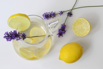 Lemonade in a glass jar with lemon slices, garnished with whole lemon and lavender flower. Top view. Photo from above. Summer fruit healthy cold drink with lemons.