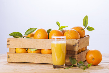 Oranges with leaves in a wooden box and orange juice.