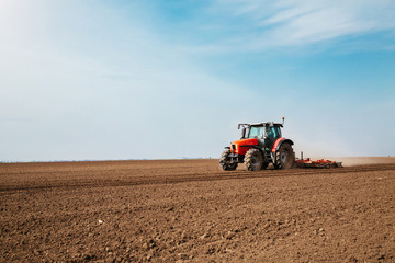 Fotomurales - Farmer in tractor preparing land with seedbed cultivator