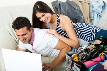 Young spouses browsing web and packing luggage