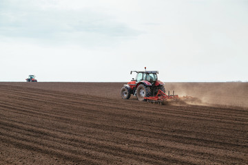 Fototapete - Tractor cultivating field at spring
