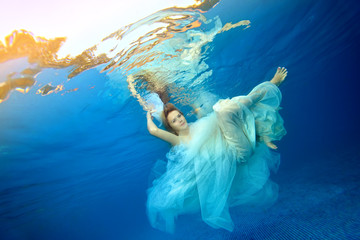 Beautiful girl dancing underwater in a white wedding dress against a blue background. Portrait. Horizontal orientation