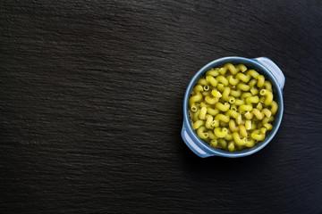 Uncooked green Italian pasta Celentani in dark blue pot on black slate stone background, top view
