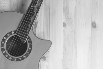 Guitar on wooden background with copy space in black and white