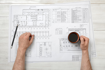 Close-up hands of man holding cup coffee over drawing layout in top view