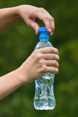 hands opening bottle with fresh water