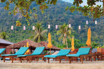 asian tropical beach with sunbeds under trees, Thailand