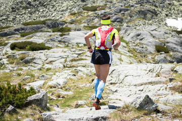 middle age man running in compress socks on hard mountain trail with big stones