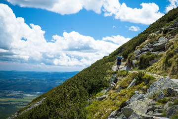 running on steep trail in mountains with view and blue sky