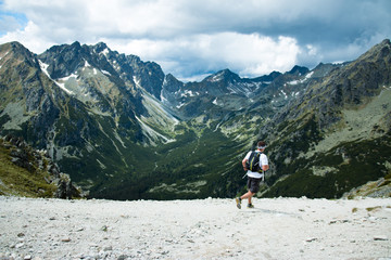 man with backpack running on the trail in epic mountain scenery with clouds and peaks